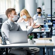 In an office setting, people are working at their laptops, wearing face masks and at separated desks. At the front of the picture, a white man is wearing a face mask and talking to his coworker, a black woman wearing a face mask. Their desks are separated