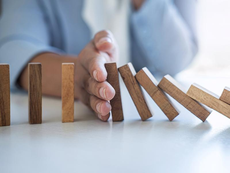 Wooden dominoes with hand stopping the fall progression