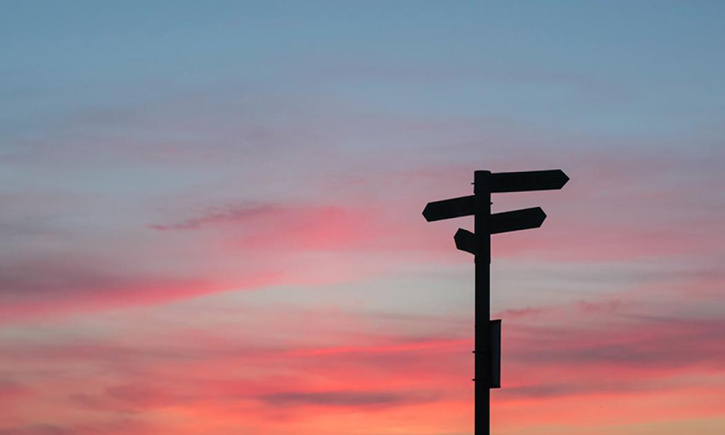 A street sign is silhouetted in black in the bottom right of the photo against a sunset sky in the background.
