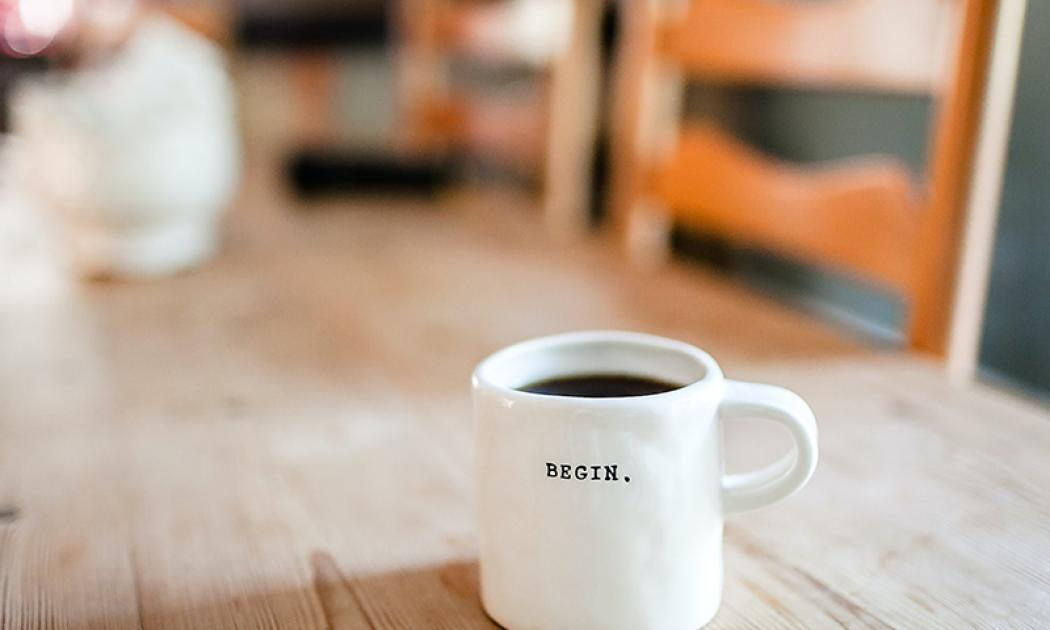 "Coffee cup with the word ""Begin"" on a wooden table"