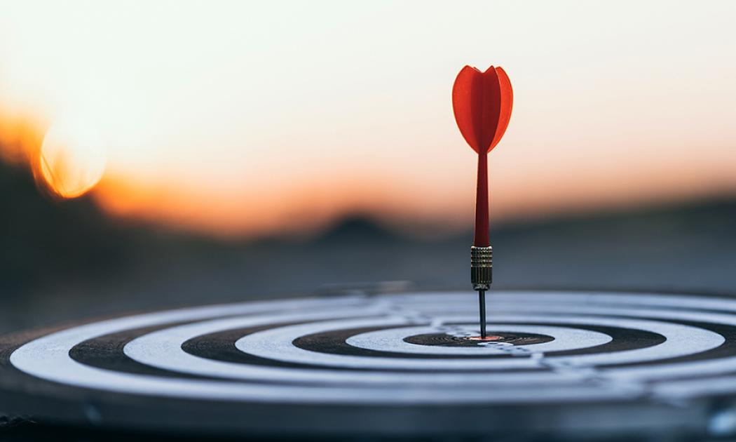 Dart on a horizontal dartboard with sunset in the background