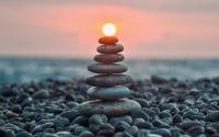 a Cairn on a beach of rocks with the ocean and sunset in the bakcground