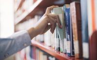 Hand reaching for a book on a library shelf