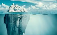 Iceberg in a calm ocean, small bit above water, much larger portion below