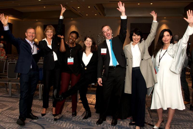 A group of smiling people, at an event, raising their hands